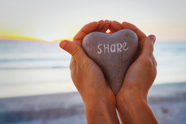share concept, hands holding stone with word written on it